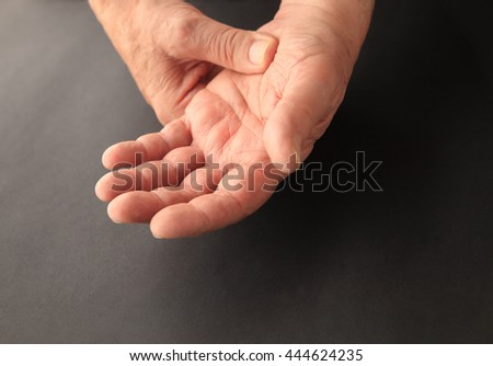 A senior man grips his sore hand on a black background with copy space. - stock photo