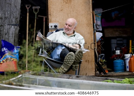 A senior man having a break on an allotment, reading a newspaper - stock photo