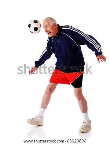 A senior man heading a soccer ball.  Isolated on white. - stock photo