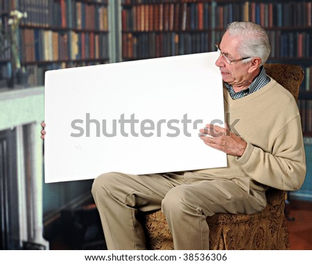 A senior man holding a blank sign in his home library/office.