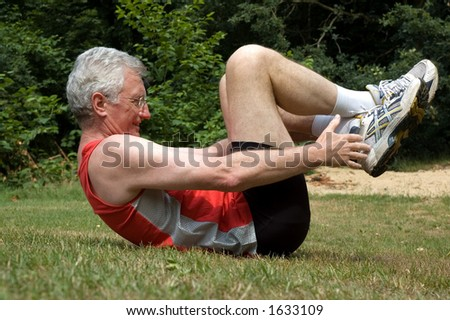A senior man is stretching after a long run - stock photo