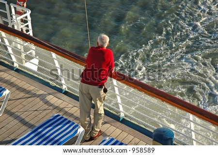A senior man looks out over the rail of a cruise ship - stock photo