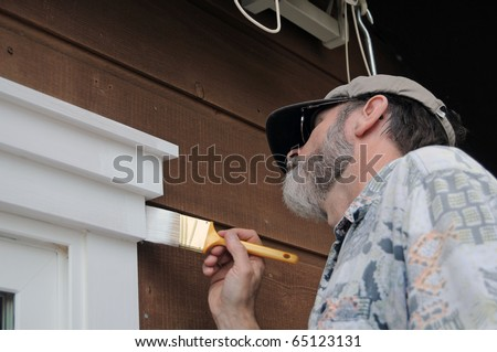 A senior man painting the doorway with white paint - stock photo