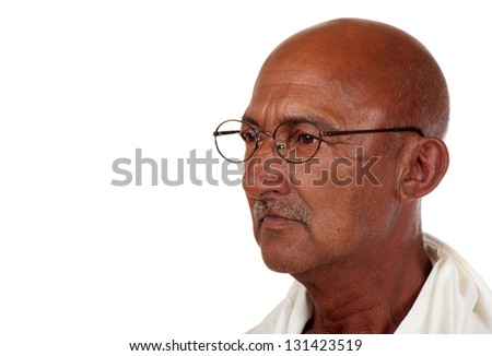 A senior man peers through his spectacles as if in deep thought. - stock photo