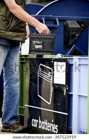 A senior man recycling a car battery, close-up - stock photo