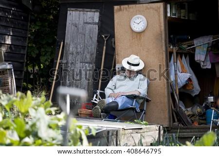 A senior man resting on an allotment - stock photo