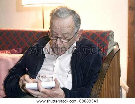 A senior man sits and writes on a pad.