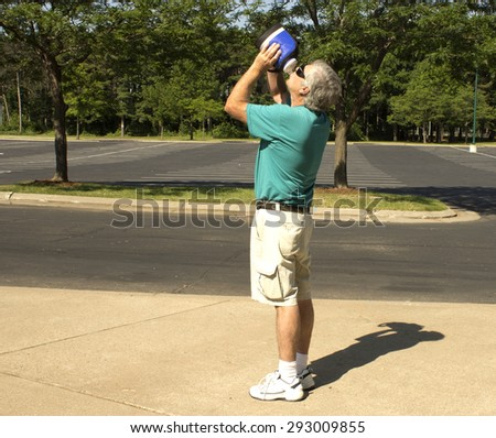 A senior man stops to take a drink of water while out on a walk - stock photo