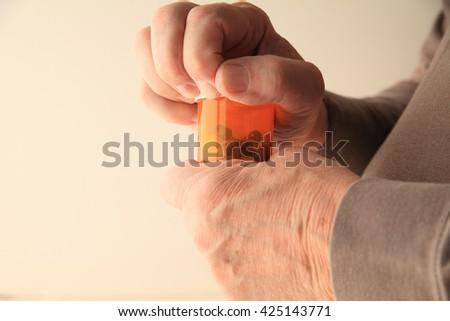 A senior man struggles to open his prescription capsules. - stock photo