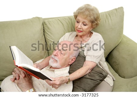A senior man taking an afternoon nap while his wife reads to him.  White Background. - stock photo