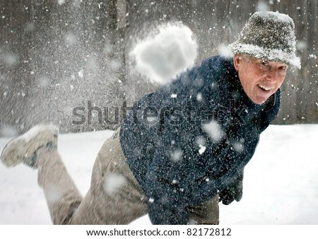 A senior man throwing a snowball - stock photo