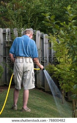 A senior man watering the lawn. - stock photo