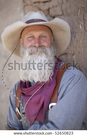 A senior man with a white beard is leaning against an adobe brick wall and looking at the camera. Vertical shot. - stock photo