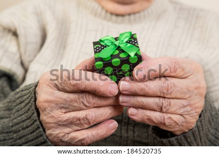 a senior person holding a gift pack