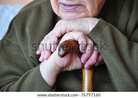 a senior person leaning on a wooden cane - stock photo