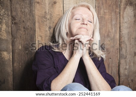 A senior person pray with a wood background - stock photo