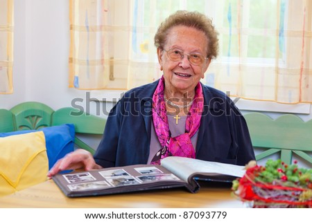 a senior puts on a photo album. sitting at a table. - stock photo