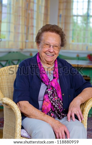 a senior sitting in an armchair and looking forward. - stock photo