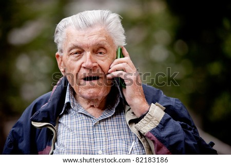 A senior talking on a cell phone outdoors - stock photo