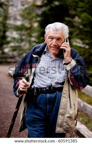 A senior talking on a cell phone outdoors in the forest - stock photo
