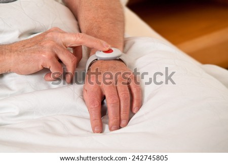 a senior with rufhilfe emergency phone in bed - stock photo