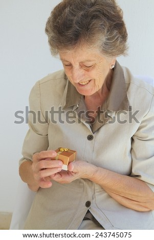 A senior woman between 70 and 80 years old is happy to get a small present box. - stock photo