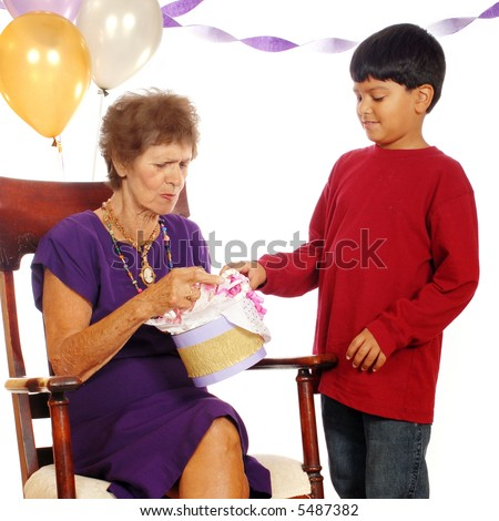A senior woman carefully opening a gift her great grandson has given her at her 80th birthday party. - stock photo