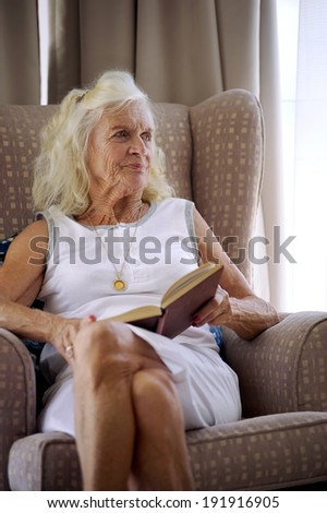 A senior woman holding a novel while sitting on her couch - stock photo