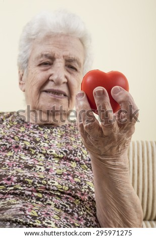 a senior woman holding a red heart - stock photo