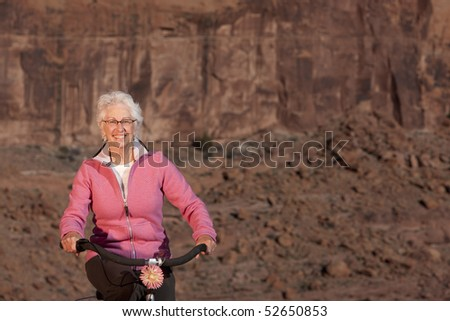 A senior woman is smiling as she rides her bike in a desert setting. Horizontal shot. - stock photo