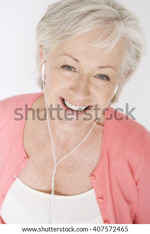 A senior woman listening to music on an mp3 player