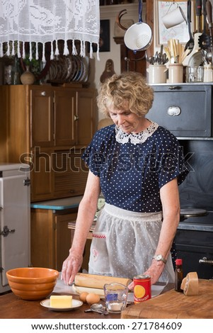 A senior woman making a pie in clothing and kitchen in the 1940's - stock photo