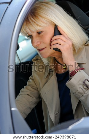 A senior woman  phoning at the wheel of her car. - stock photo