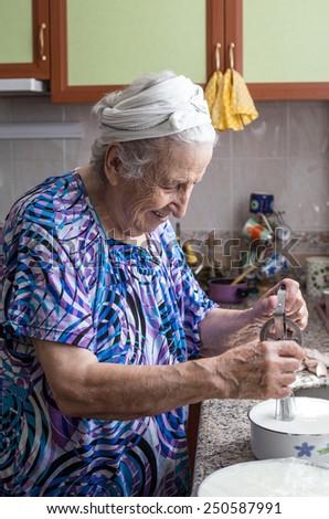 a senior woman preparing food in kitchen - stock photo