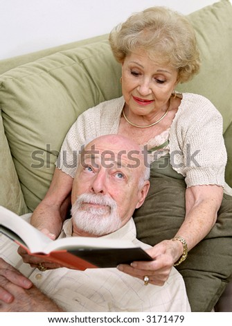 A senior woman reading to her husband who is rolling his eyes in boredom. - stock photo