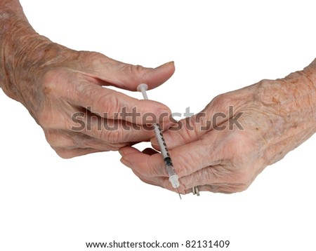A senior woman's hands holding a syringe, isolated on white - stock photo