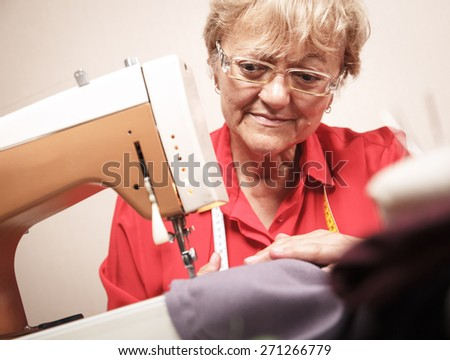 A senior woman sewing on a sewing machine. - stock photo