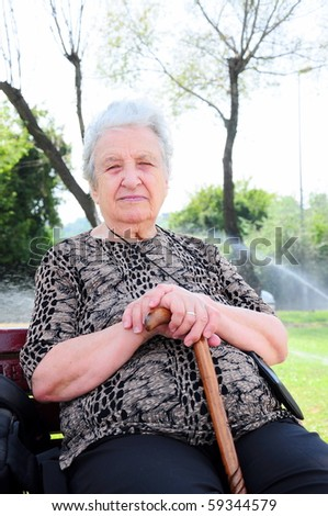 a senior woman sitting in a park with her stick/cane - stock photo