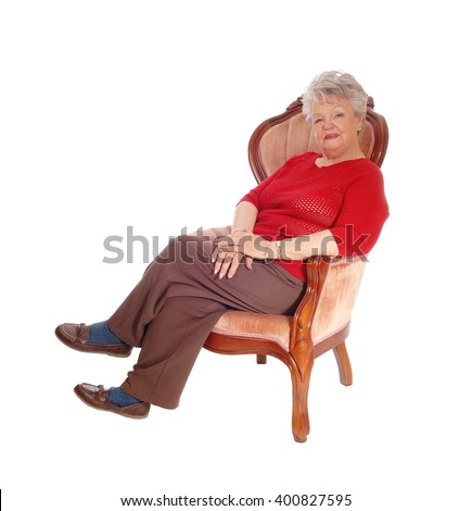 A senior woman sitting in a pink armchair in a red sweater and brownpants, isolated for white background. - stock photo