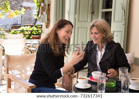 A senior woman, 61, sitting with her friend, 46 years, at a greek coffee shop, outdoors, having greek hot coffee, looking photos with a mobile.