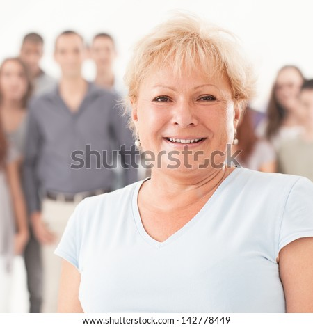 A senior woman smiling and standing in front of a large group of people. - stock photo