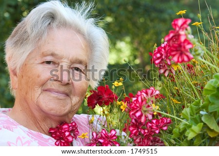 A senior woman standing by flowers - stock photo