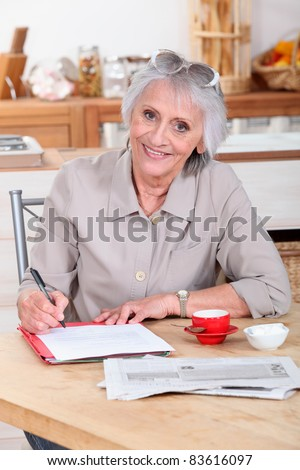 a senior woman writing a letter - stock photo