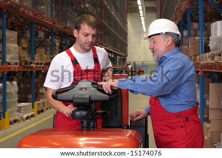 A senior worker teaching his junior the operation of a fork lift vehicle in a factory - stock photo