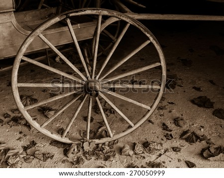 A sepia toned old fashioned cart wheel on rustic floor with leaves. - stock photo