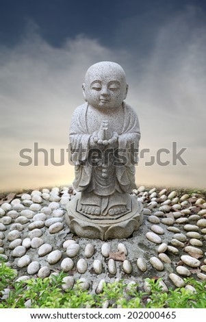 A serene meditating baby monk against a dreamy surreal cloudscape.  - stock photo