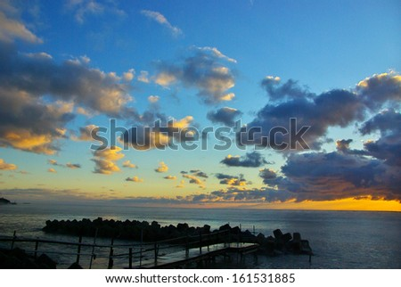 A serene sunset by a dock with low clouds. - stock photo