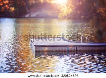 a serene view of a peaceful dock in a misty atmosphere on calm water during morning sunrise or evening sunset toned with a retro vintage instagram filter effect app or action - stock photo
