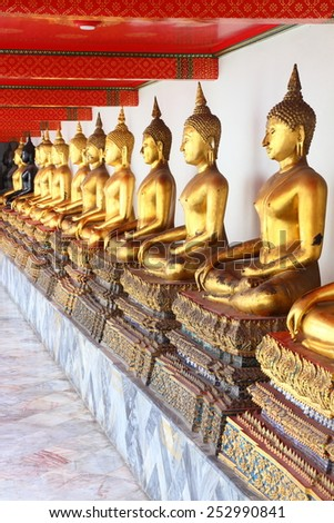 A series of ancient golden Buddha statues lined up in a row. A beautiful collection of symbolic Buddhist idols. - stock photo