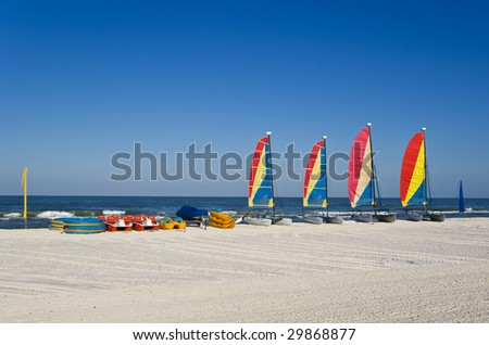 A series of colorful pedal boats, kayaks and catamaran sail boats at a resort. Blue sky and turquoise sea. Plenty of space for copy. - stock photo